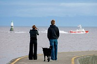 A young couple watches the Victoria BC harbour Pilot boat return to port from the Ogden Point breakwater, Victoria, Vancouver Island, British Columbia...