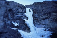 Man climbing icefalls in Ghost River, Alberta, Canada