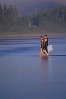 young couple with boogie board, Longbeach, Tofino, Vancouver Island, British Columbia, Canada