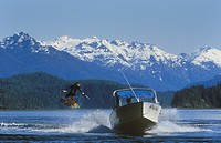 Wakeboarder taking a ride with mountains beyond near Tofino, Vancouver Island, British Columbia, Canada