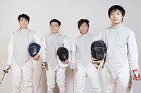 Portrait of four male fencers holding fencing foils and fencing masks
