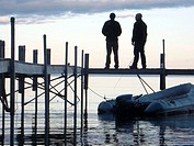 Small dock with people walking on it at sunset in Sebago Lake, Maine
