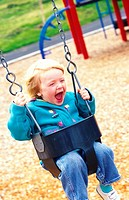 Laughing Child Swinging at Playground