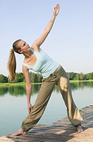 Woman 20-25 exercising yoga on jetty