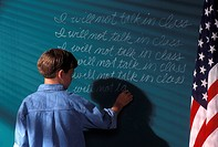 Boy Writing On Chalkboard As Punishment