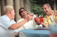 Men Laughing And Toasting Each Other At Sidewalk Cafe