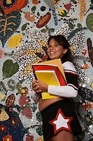 Side profile of a girl holding books and smiling