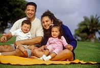 Family Sitting On A Blanket In The Park And Smiling