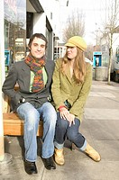Fashionable Caucasian Girl Sitting On A Bench With Her Hip Boyfriend