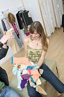Handing A Pile Of Clothes To A Stylish Girl In A Fashionable Boutique
