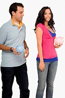 Young couple holding piggy banks