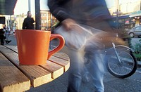 Coffee Mug on a Sidewalk Cafe Table With Pedestrian in Background