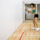 Woman playing racquetball in indoor court, portrait