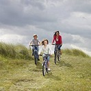 Mother with son and daughter 10-12 riding bikes on meadow