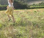 Teenage girl 16-17 skipping in meadow, rear view