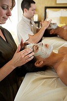 Couple receiving facial treatment in spa