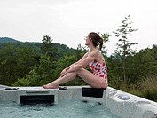 Mature woman sitting at edge of jacuzi, side view, looking away