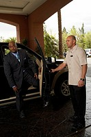 Hotel porter opening car door for business man