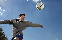 Young man looking at football in air blurred motion