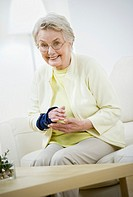 Senior woman with wrist brace sitting at home, portrait