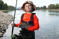 Portrait of boy 6-7 posing with fish and fishing rod in river