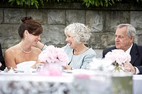 Bride celebrating with guests at wedding reception, smiling