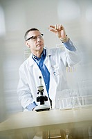 Mature male doctor standing by microscope, looking at specimen