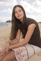 Young woman sitting at beach, portrait
