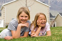 Girls 8-11 lying on grass with house in background, portrait