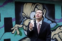 Businessman Eating Snacks and Listening to Music