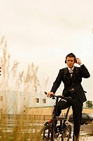 Businessman on Bicycle Wearing a Headphone