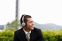 Smiling Businessman Listening to Music