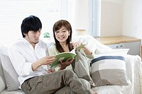 Couple Reading a Magazine on Sofa