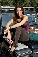Woman sitting on the hood of an SUV holding a cellular phone smiling (thumbnail)