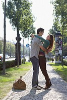 Couple embracing on a sidewalk smiling