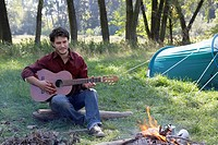 Man at campsite playing guitar and smiling