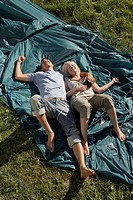 Couple lying on unraised tent smiling with the woman holding mallet
