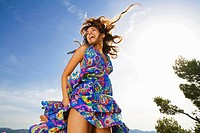 Woman laughing outdoors in a colorful dress