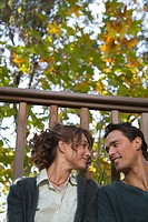 Couple outdoors on balcony sitting together and smiling