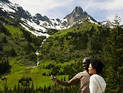 Couple taking self portrait with digital camera, mountains in background, side view