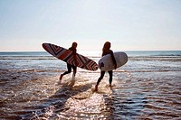 Couple running in water carrying surfboards