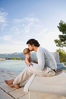 Man kissing a baby by an infinity pool