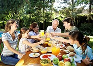 ´Family, including children 7-11 sitting at table in garden, toasting with orange juice and smiling´