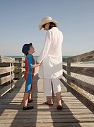 Mother and son 4-5 talking on boardwalk leading to beach, rear view