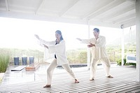 Woman doing tai chi with teacher on porch