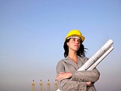 Woman in hard hat holding drafts with towers in background