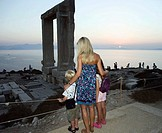 Woman with young boy and young girl looking at The Portara in Greece with tourists in background