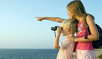 Young girl pointing out over the sea smiling with young boy using binoculars