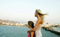 Woman and young girl looking over the water in Greece