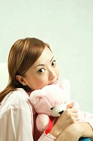 Woman in pajamas hugging teddy bear